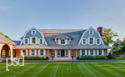 9) Two classic shingle style gambrel roofs run perpendicular to the main body of the house and flank an entry porch with two robust columns.