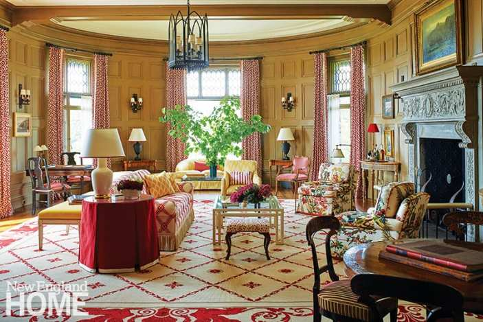 """A needlepoint rug by legendary twentieth-century designer William """"Billy"""" Haines anchors the vast living room. A custom lantern was designed to harmonize with the original sconces. The sofa is covered in Brunschwig & Fils's Bamboo Trellis, while the pair of club chairs features Le Lac glazed chintz by the same fabric house. The coffee table is by Billy Baldwin Studio."""