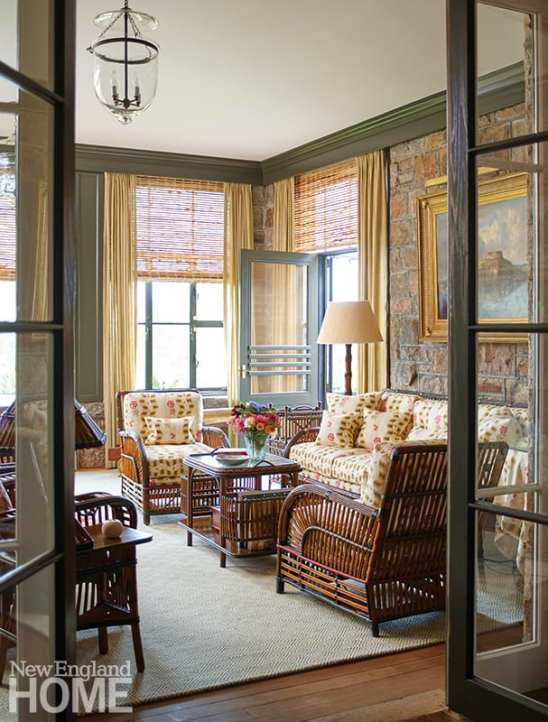 The rock porch features 1920s Arts and Crafts rattan furniture with cushions upholstered in Stroheim's Dauphine pattern. A Rose Cumming fabric was used for the curtains to frame the surrounding vistas.