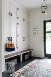 Cabinet doors conceal the inevitable chaos of messy coats and other clutter in a family-friendly mudroom.