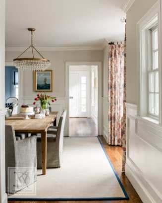 One of the requests for this full-home renovation was a formal but approachable dining room. A floral Cowtan & Tout fabric used for the drapery inspired the warm color-scheme while an informal pine table and upholstered chairs make the space feel cozy and welcoming.