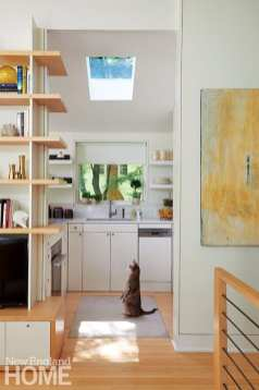 Zeus the cat approves of the home's special touches, like the maple wraparound shelves at the kitchen's entrance.