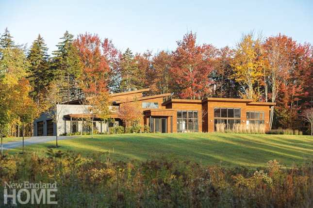 Massive windows fill the five-bedroom home with light and take advantage of the sloping lot's close and distant views, while stained cedar siding allows it to comfortably blend in with its forested location.