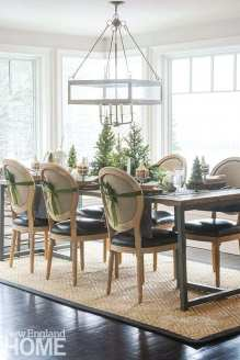 Sigman sets tables throughout the house; in the kitchen, the floral designer ran a simple centerpiece of fresh treetops surrounded by princess pine along the table to encourage the flow of conversation.