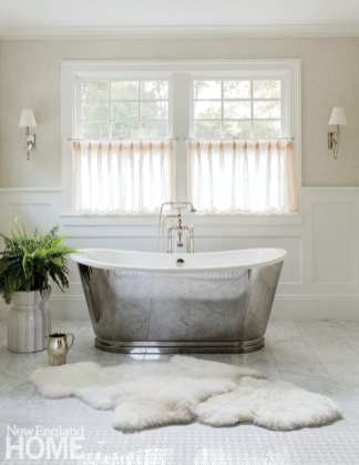 A mirrored soaking tub that nods to the antique and a classic marble floor bring the glamour.