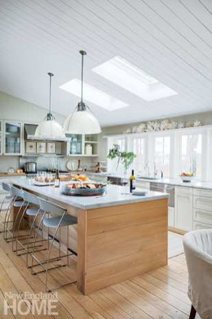 Aged French oak floorboards wrap the kitchen island and repeat on the dining room fireplace. The linear pattern echoes on the ceiling's shiplap and on the sailor-striped floor rug.