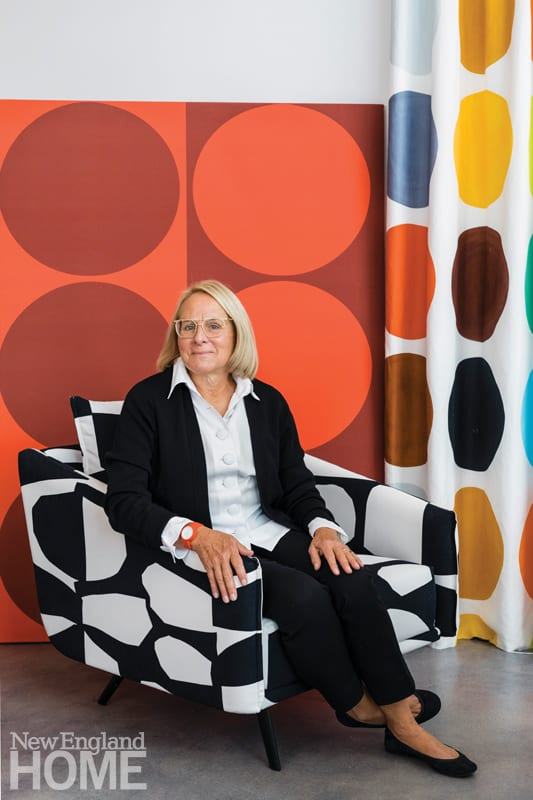 Artist Liz Roach sitting on a chair upholstered with one of her fabric designs.