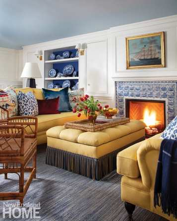 Golden yellow fabric adds a sunny note to the sitting area; the Schibanoffs collected the Delft tiles around the fireplace over the years.