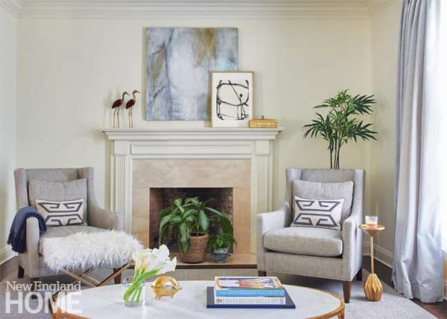 Two gray chairs flanking a fireplace
