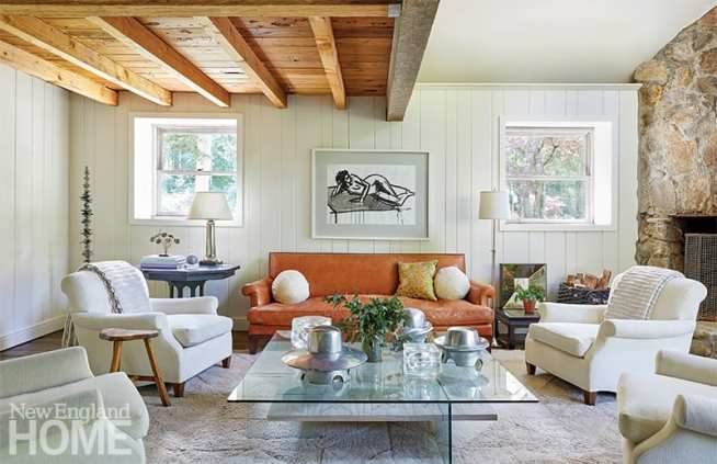 Living room with leather sofa and white chairs.