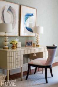 In the main bedroom, artwork by Rebecca Stern hangs above a chair and vanity from Hickory Chair.