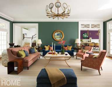 Throughout the residence, architect Judy Larson employed traditional details such as dentil moldings and transom windows. At the request of the clients, who have young children, designer Kathleen Walsh added warmth to the architecture through her bold use of color. A striking chandelier from McLain Wiesand illuminates the living room, which is painted Benjamin Moore Caldwell Green.
