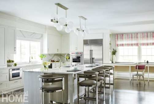 """A ten-foot-long kitchen island doubles as a dining counter and an accessible workstation for the owner; """"my client loves bubbles,"""" says Rapp, """"so we chose two of the large Hinsdale light pendants from Hudson Valley over the island."""""""