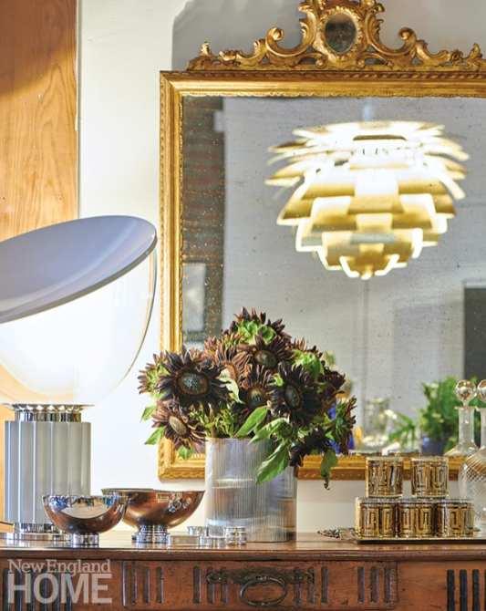 A gilt rococo mirror reflects a vintage artichoke-style pendant.