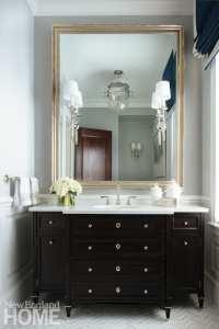Formal bathroom with dark vanity and light walls.