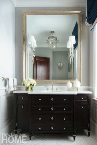 Formal bathroom with dark vanity and light walls.