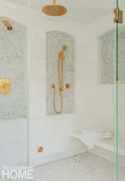White tiled shower with gold fixtures