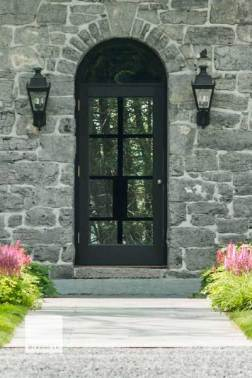 This traditional door features true divided light, and a curved jamb scribed to the restored stone opening. While it may look similar to the century-old door it replaced, modern thermal barriers such as low- E coated insulated glass units, an active sweep and high quality silicone gasketing ensure that it meets the requirements of current energy-efficient building practices. Photo by Jim Westphalen.