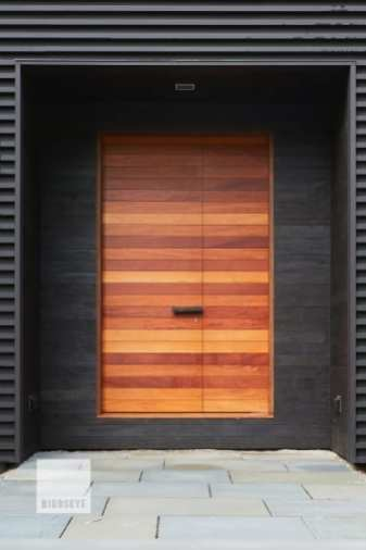 Making a colorful statement, this mahogany-clad set of doors stands out against a charred shou sugi ban and black metal surrounding. The offset split between leaves and a custom handle add visual interest. Like many of our larger doors, this door utilizes a multi-point latching system for stability and security. Photo by Erica Allen