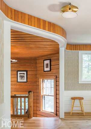 When the home's boathouse was refurbished, some of its wood paneling was salvaged and applied in a ribbon frieze along the top of the game room wall. It perfectly matches the antique wood paneling of the staircase.