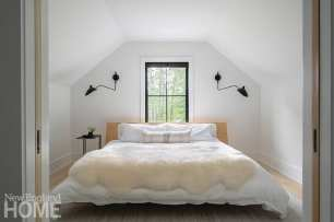 A pair of compact upstairs bedrooms with pocket doors accommodate overnight guests while taking maximum advantage of the structure's limited allowable footprint.