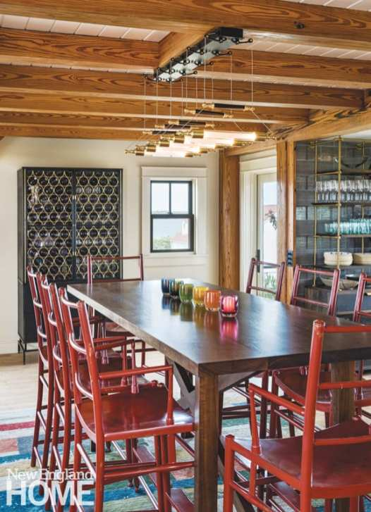 Rustic dining area with wooden beams and red chairs.