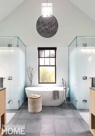 In the main bath, a light fixture from Design Within Reach makes a statement above a Waterworks tub flanked on the right by a shower and on the left by a water closet.