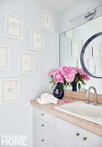 The design team left the bathroom's existing pink tile and wall mirror in place; a modern round mirror, new lighting, and subtly humorous artwork (sketches of superheroes using the toilet) freshen up the area.