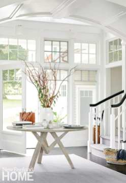 All white entryway with round table.