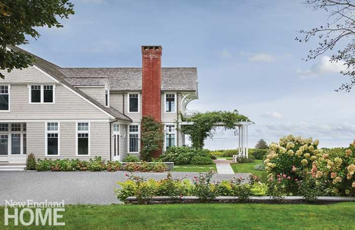 Newport shingle style home with a rose covered pergola