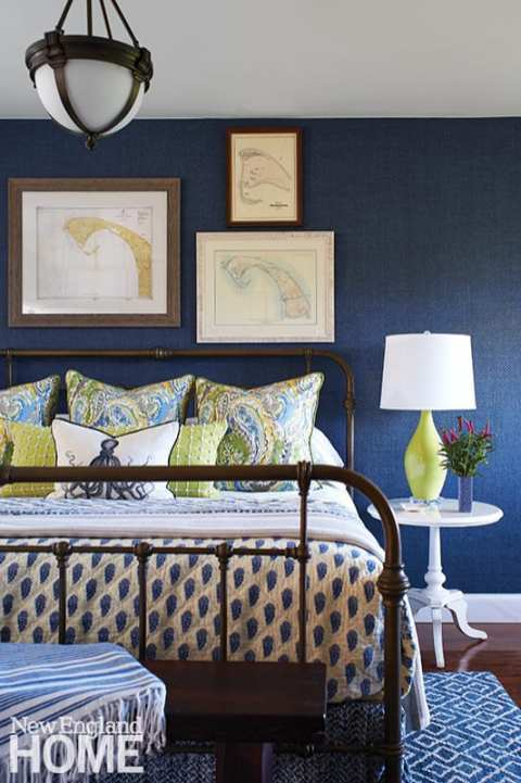 Bedroom with blue wallpaper and paisley bedding.