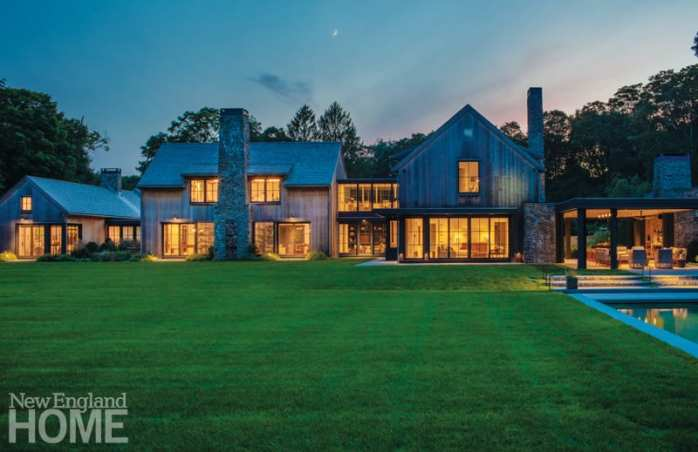 Native ledge resting just below the earth's surface provided both inspiration and building material for this Fairfield County house. Viewed here from the rear, the home's outdoor kitchen and seating area, saltwater pool, and spa double down on its connection to the outdoors.
