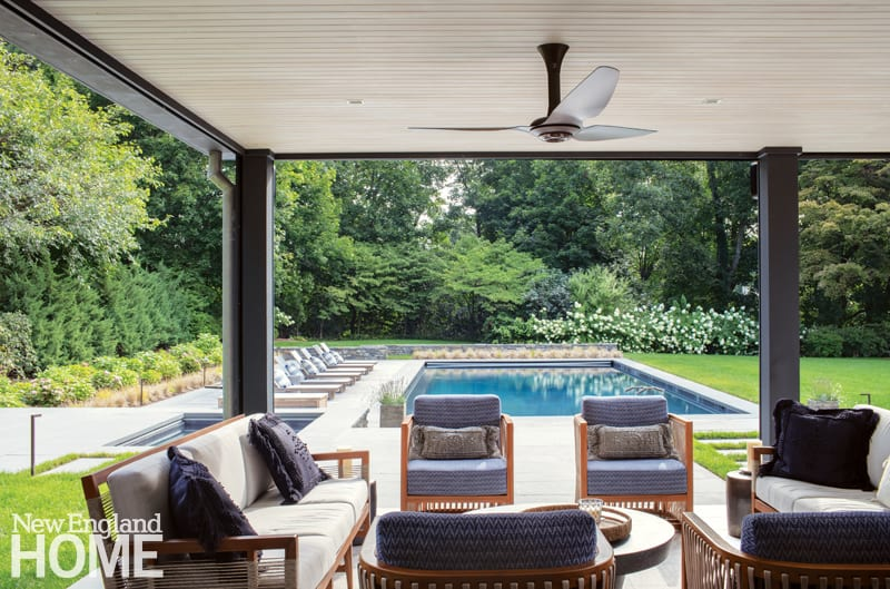 At dusk, retractable screens offer insect protection on the poolside patio. The deck of the spa on the left is set about two feet higher than that of the pool, making entrances and exits easier.