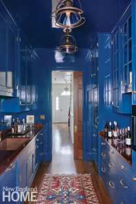 A high-gloss hallway serves as a moody, sophisticated bar with generous storage space. The pendants come from Millerton Antiques Center.