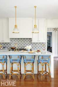 The bright blue hue of the Glac Seat bistro counter stools coordinates with the backsplash tiles from Country Floors.