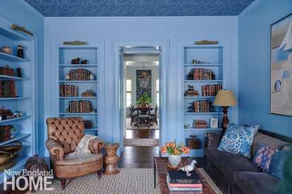 The inviting library features saturated colors, rich vintage leather, Schumacher wallpaper on the ceiling—and an enticing peek into the dining room. There's artistry in the details, from the classically styled shelves to a vase that echoes the Greek-key pattern in the Jonathan Adler rug.