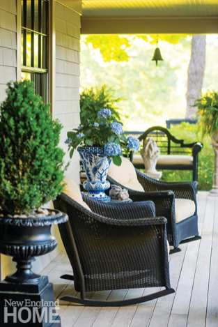 Two brown wicker rocking chairs on a deck