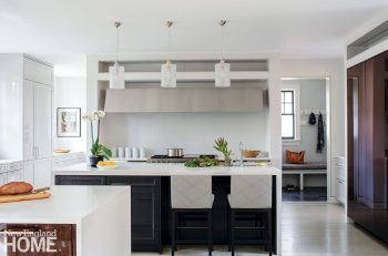 White kitchen with a marble topped island.