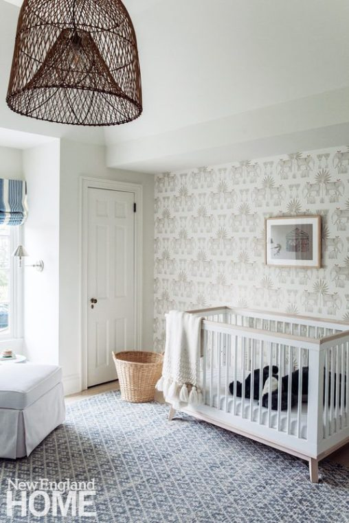 Baby nursery with a contemporary crib and patterned wallpaper.