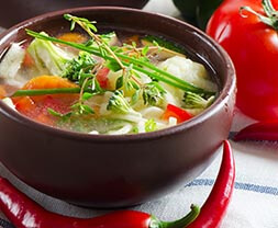 Bowl Of Vegetable soup with fresh herbs and chicken