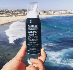 person holds travel size NeilCleanse bottle next to ocean