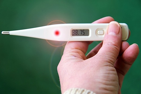 hand holds thermometer showing a fever