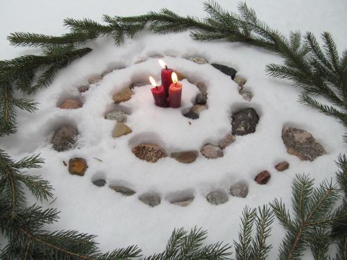 Ofrenda con piedras, velas y motivos vegetales para Yule en el solsticio de invierno