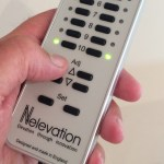 Nelevator remote control held in hand with two LEDs illuminated