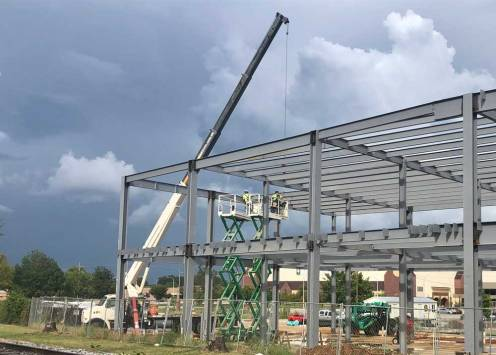 NEmiss.News Workers building steel structure