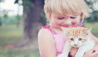 child with a pet cat