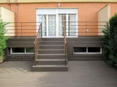 tarima madera exterior en zona de terraza con escaleras acceso a vivienda.