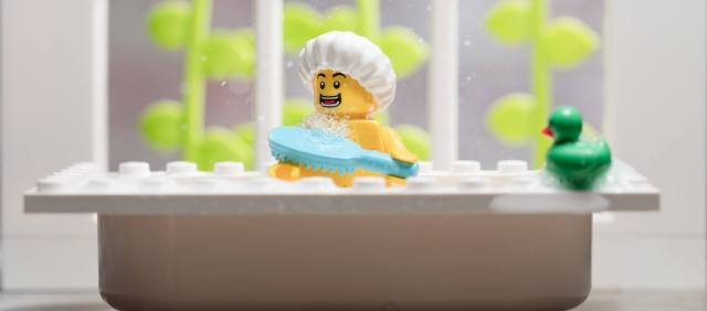 A LEGO in the bathtub, bathing with his duck.