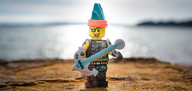 A photo of a LEGO who is part pirate and part musician.