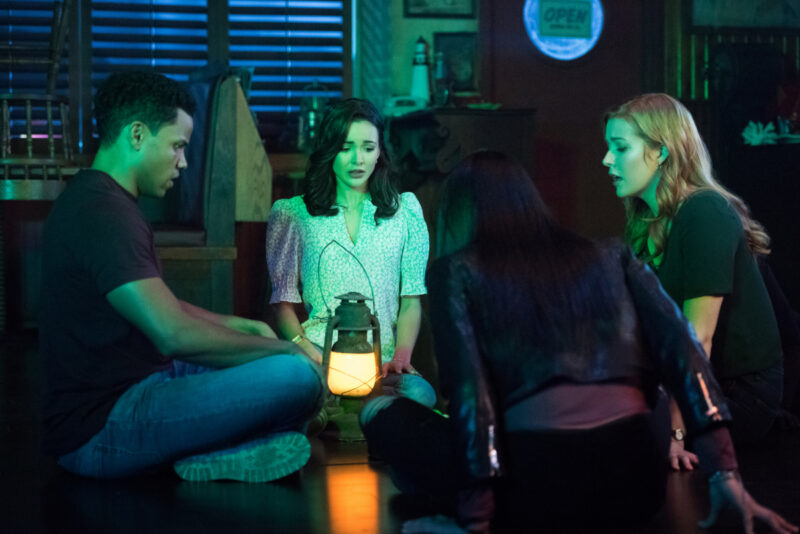 Promotional image from The CW's 'Nancy Drew' series. Nick, Bess, Nancy and George sit on the floor in a circle with a lamp between them.